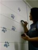 Painting paw prints on nursery wall